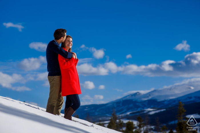 Sapphire Point Engagement Photography Session - Kisses in the snow wearing a read winter coat as Breckenridge resort is seen in the background