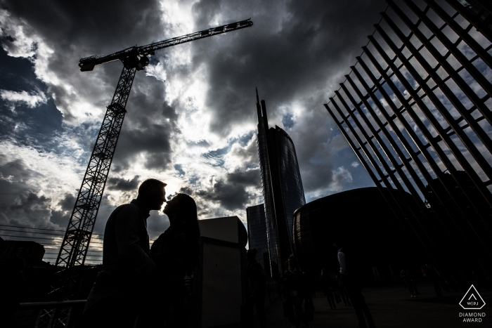 Black and white engagement photo of a couple silhouetted beneath a construction crane in Milan, Italy.