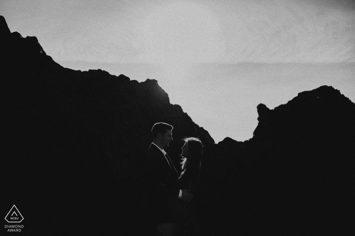 Black and white engagement session of a couple standing together in front of a large rock formation in Bodega Bay, CA.