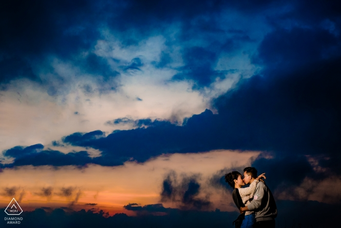 Engagement photoshoot of a couple kissing at dusk beneath blue clouds in Dalat.