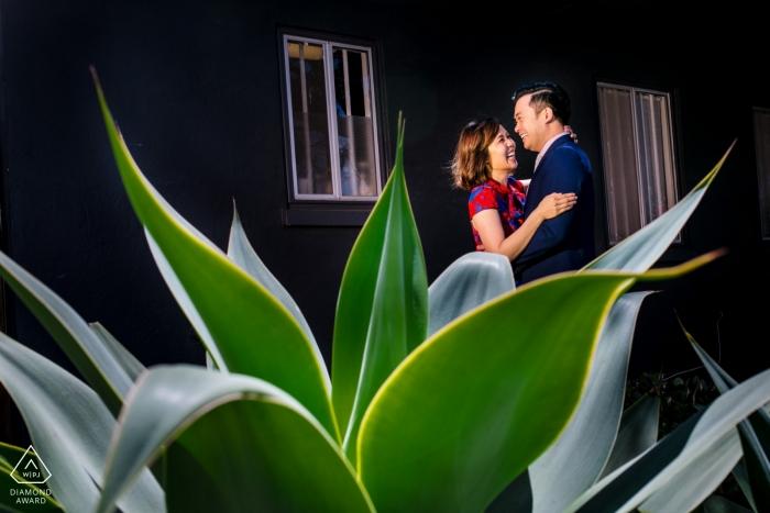 Verpflichtungsporträt eines Paares genommen mit einer Anlage im Vordergrund in Venedig, CA.