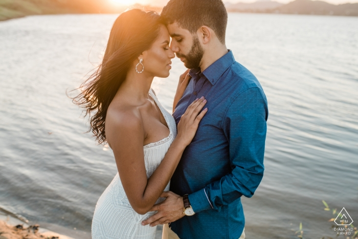 Macae engagement photography session captures the couple embracing in front of a pond while the sun sets behind them