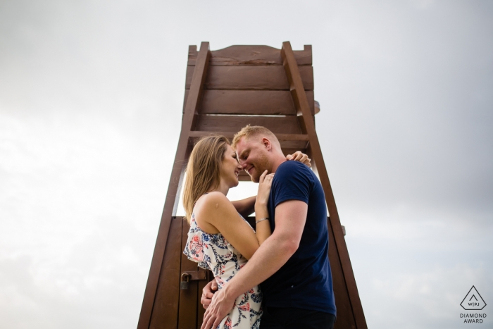 Couple kiss behind a lifeguard stand in this Playa del Carmen engagement photo shoot