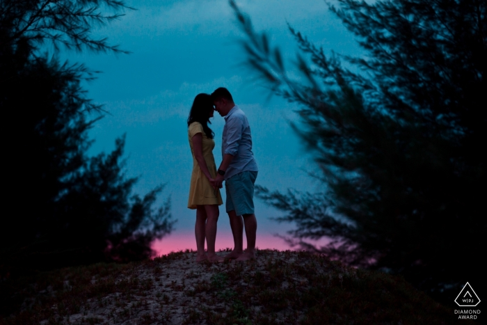Couple hold hands in front of a beautiful dusk sky in this Malaysia pre-wedding shoot