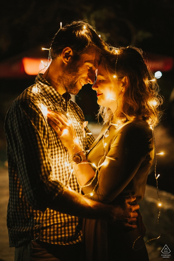 Topoľčany, Slovakia - couple drapes themselves in strands of lights while embracing for their engagement photoshoot