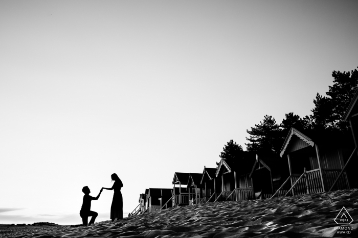 Wells-next-the-Sea, United Kingdom - man poses on one knee next to his future bride as a row of shacks line the beach in this black and white engagement photography session