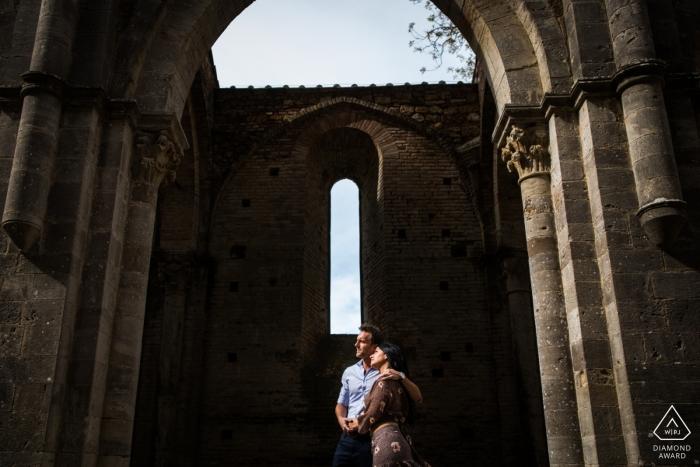 Abbazia di San Galgano engagement portrait of a couple under the arch