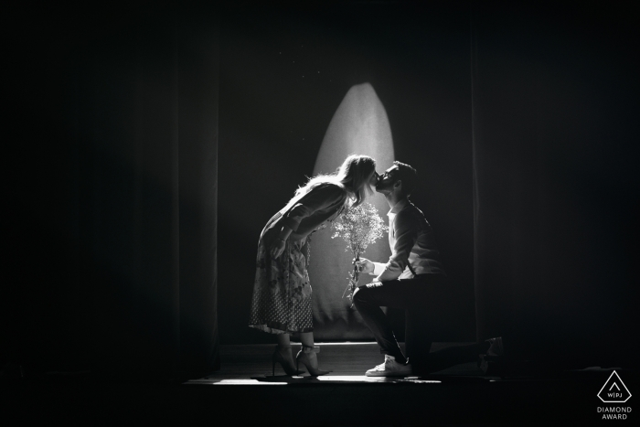This black and white photo of a couple kissing was captured during an engagement photo session that took place at the municipal theater of Alvito