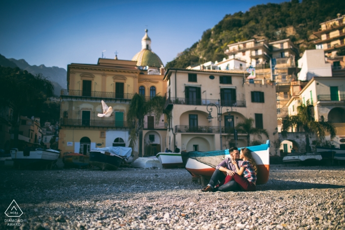 Salerno engagement photo shoot captures the couple sitting on the ground next to a red striped row boat