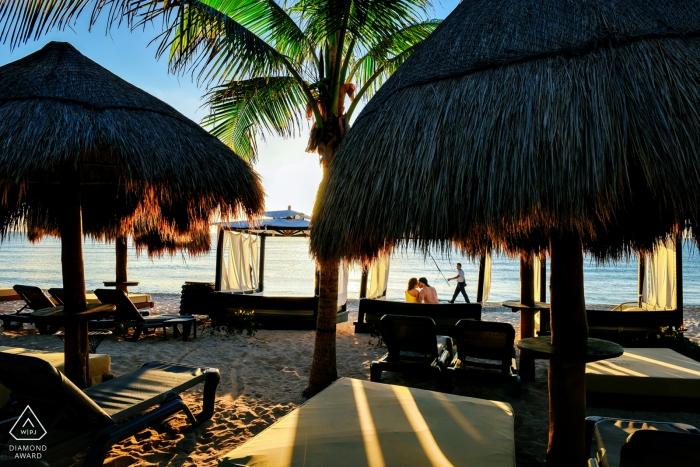 Playa del Carmen, Mexiko - Paar beobachtet den Sonnenaufgang an einem Strand voller leerer Cabanas in dieser Verlobungsfotosession