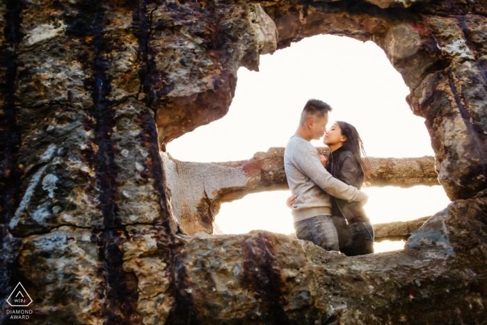 Le photographe jette un œil à travers une fissure dans le mur de béton pour capturer le couple qui s'embrasse lors de cette séance photo de fiançailles à San Francisco