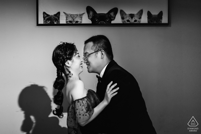 Fujian, China- the happy couple is seen embracing under a picture of a dog and cats in this black and white pre-wedding portrait