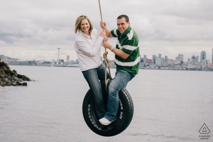 Photo de fiançailles de West Seattle, Washington, avec un couple balançant un pneu temporaire au-dessus de Puget Sound