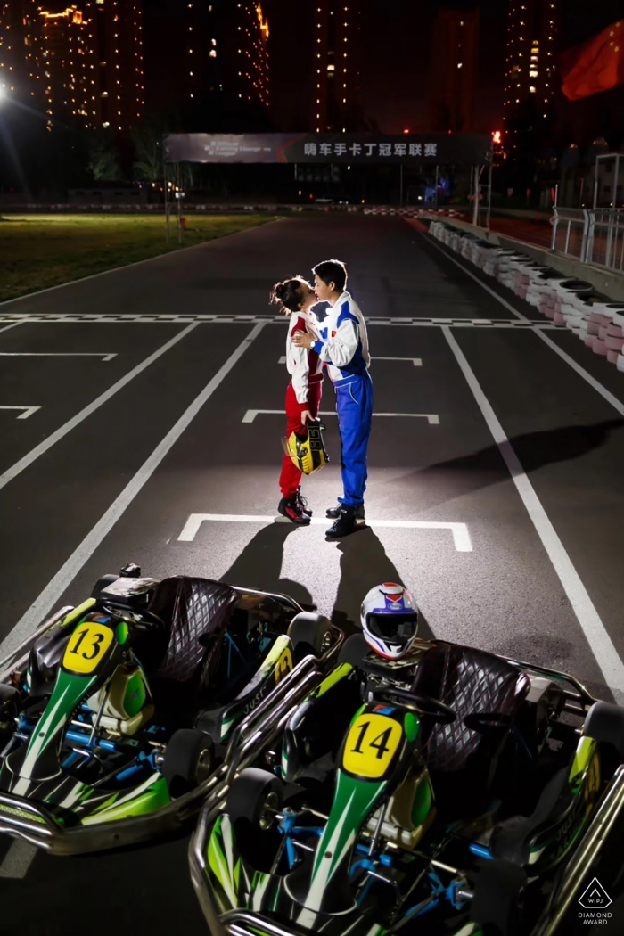 A couple kisses in racing gear on a race track at night in this engagement photo session by a Shandong, China photographer.