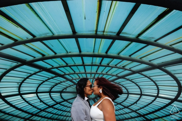 A couple kisses beneath a spiral window and blue skies in Colombo this engagement photo session by a Sri Lanka wedding photographer.