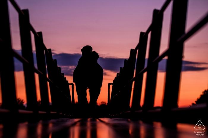 Un couple se tient dos à dos au coucher du soleil lors de cette séance de fiançailles à Arlesey, réalisée par un photographe du Bedfordshire, en Angleterre.