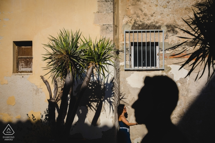 A woman stands holding the large shadow of a man's chin on Orgigia Island during their engagement photoshoot by a Syracuse, Sicily photographer.