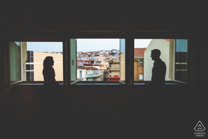 Ein Mann und eine Frau werden durch die Fenster in ihrem Haus in Pachino in diesem Verlobungsfoto von einem Fotografen aus Syrakus, Sizilien silhouettiert.