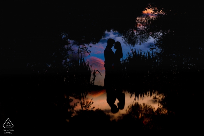 The bride and groom's silhouettes are reflected in a pond in during this London, evening engagement shoot by an England photographer.