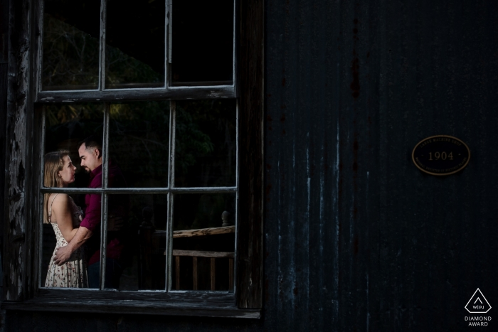 A man and woman can be seen holding one another through a window during their engagement session in Fort Myers by a Key West, FL photographer.