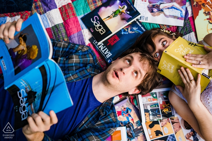Couple lays among anime and graphic novels during engagement portrait session in Balboa Park, San Diego