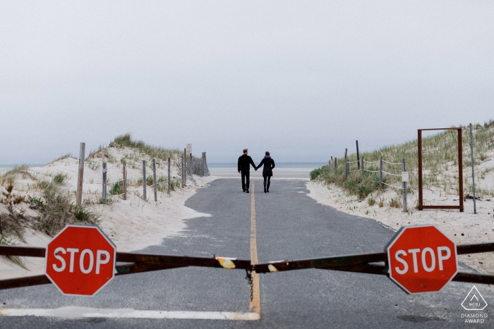 A couple walks hand in hand down the road with two stop signs behind them in Cape Cod in this engagement photo by a Boston, MA photographer, who is also available for RI, VT, NH and CT weddings.