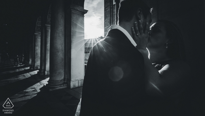 A couple kisses as the sun beams through large columns in this black and white pre-wedding portrait by a Venice, Veneto photographer.
