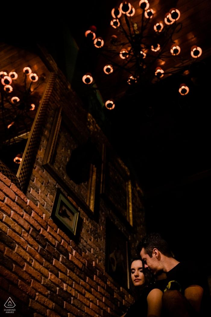 A couple stands together next to a brick wall beneath a chandelier in Rio das Ostras for their pre-wedding photoshoot by a Rio de Janeiro photographer.
