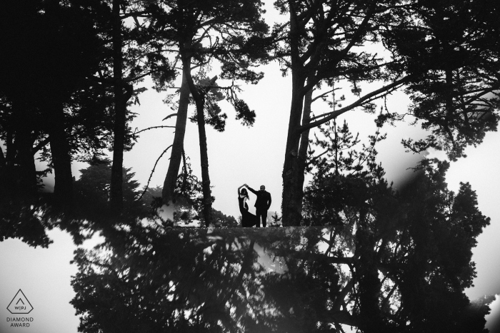 A man twirls a woman as they stand among tall trees in San Francisco in this black and white engagement photo by a Sacramento, CA photographer.