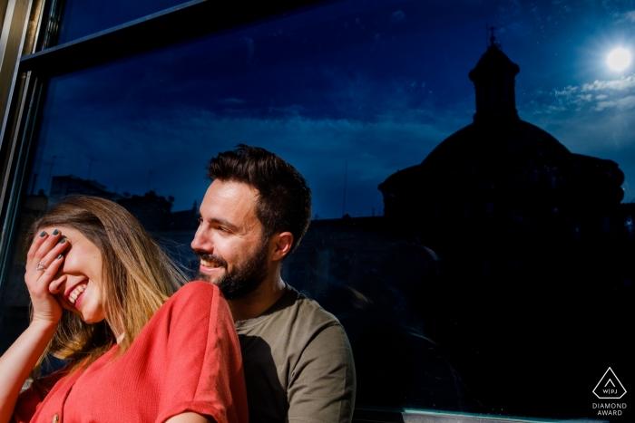 Un homme et une femme rigolent alors qu'ils se tiennent devant une fenêtre la nuit lors de cette séance photo précédant le mariage par un photographe de Alicante, Valence.
