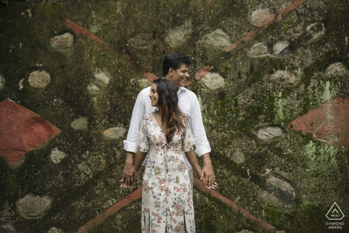 A couple poses together in front of a unique design in the Parque Lage in this engagement photoshoot by a Rio de Janeiro, Brazil photographer.