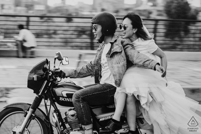 A man holds onto a woman as she rides on the back of his motorcycle during their Ho Chi Minh engagement session by a Vietnam photographer.
