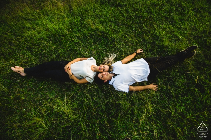 A couple lays head to head together on the grass in Ouro Preto during their engagement photoshoot by a Minas Gerais, Brazil photographer.