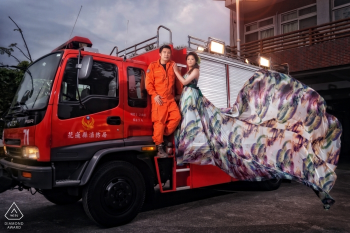 A woman's dress blows dramatically in the wind as she and her fiance stand together on a large, red truck in this engagement portrait by a Hualien County, Taiwan photographer.