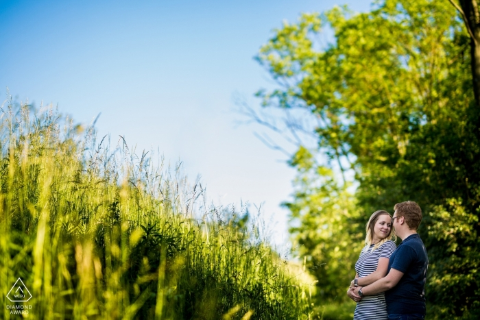 A man holds his fiance as they stand in a field in Brno in this pre-wedding photo session by a Prague photographer.