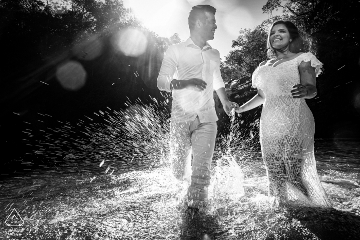 A couple runs through water in Pirenopolis as they hold hands in this black and white pre-wedding portrait by a Goias, Brazil photographer.