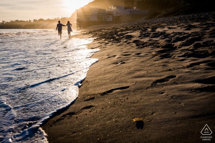 Verloofd paar die langs Malibu-strand lopen tijdens hun pre-huwelijkssessie