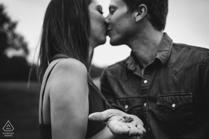 A woman in Edmonton holds a frog as she and her fiance kiss in this black and white engagement portrait by an Alberta, Canada photographer.