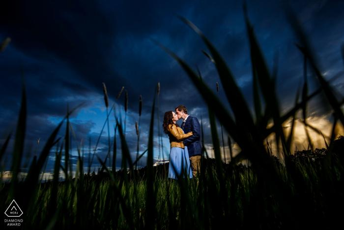 Pareja comprometida comparte un momento en Evergreen Park durante su sesión de compromiso.