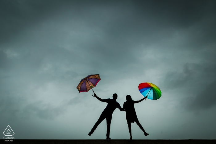 The silhouettes of the couple holding bright umbrellas against a gray sky was captured by a Mumbai engagement photographer