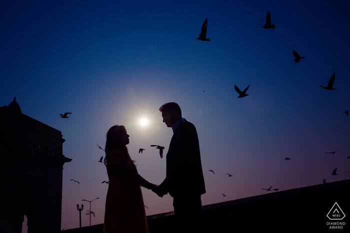 Het gesilhouetteerde paar houdt handen aangezien de vogels rond hen tijdens hun pre-huwelijkssessie in Mumbai vliegen