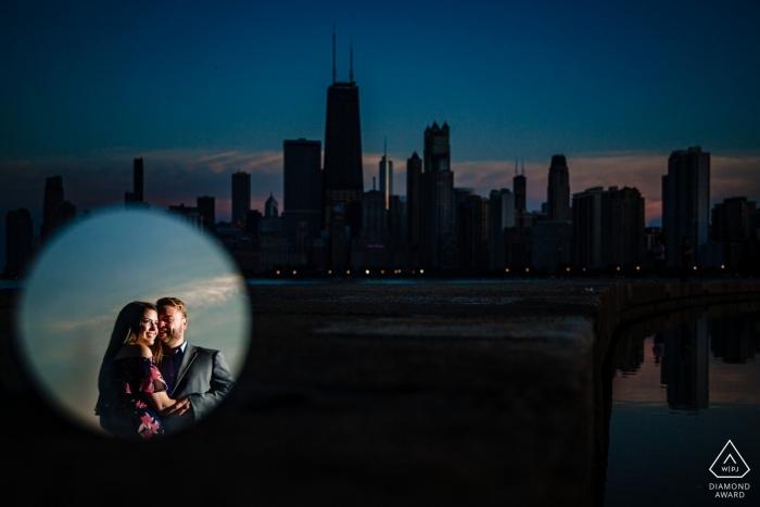 Un couple engagé se reflète dans un miroir contre l'horizon lors de leur séance de fiançailles à North Avenue Beach, Chicago