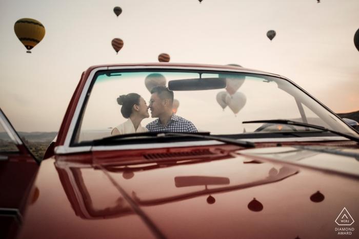 Een verloofd paar zit in de auto en kus terwijl hete luchtballonnen om hen heen vliegen tijdens hun verlovingsshoot in Turkije, Cappadocië