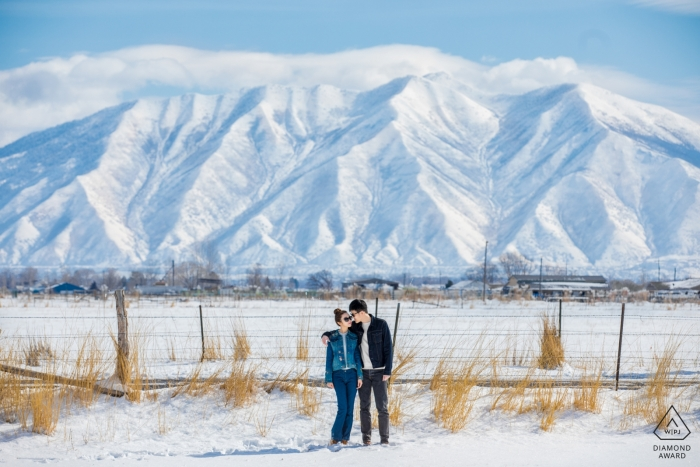 A couple poses in front of frozen mountains in the United States during their engagement photo by a Hangzhou City photographer.