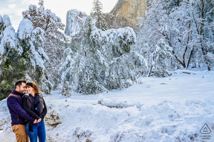 A couple stands together in front of snow-covered trees in Yosemite in this engagement photo by a Sao Paulo, Brazil photographer.