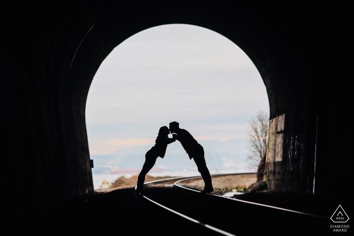 Tacoma, Washington Verlobungsfotosession | Paar lehnt sich für einen Kuss in einem alten Zug Tunnel