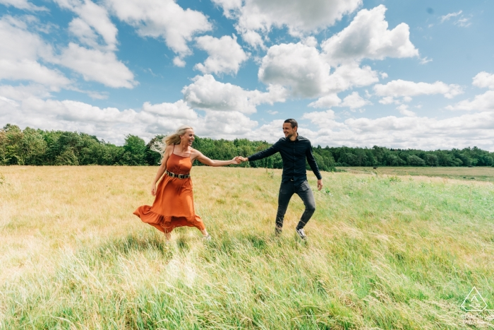 A couple holds hands under a blue sky in this prewedding portrait shot by an Overjissel engagement photographer