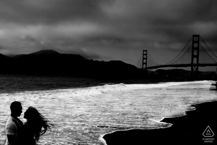 Un photographe de fiançailles à Sacramento a photographié cette photo en noir et blanc d'un couple enlacé tandis que le Golden Gate Bridge se dresse au loin