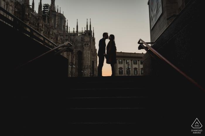 Una fotografia di fidanzamento di Napoli di una coppia che si bacia su una tromba delle scale di Milano al crepuscolo