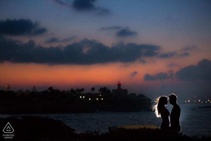 Die Sonne ist untergegangen, aber das Paar wird von einem Licht auf dem Dock in diesem Fotoshooting vor der Hochzeit in Siracusa beleuchtet